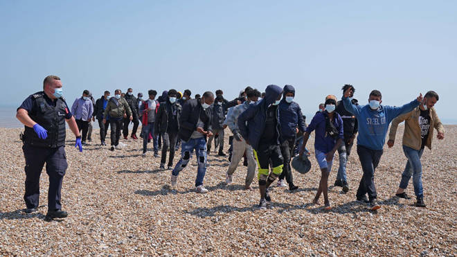 Migrants are escorted from the beach in Dungeness, Kent yesterday