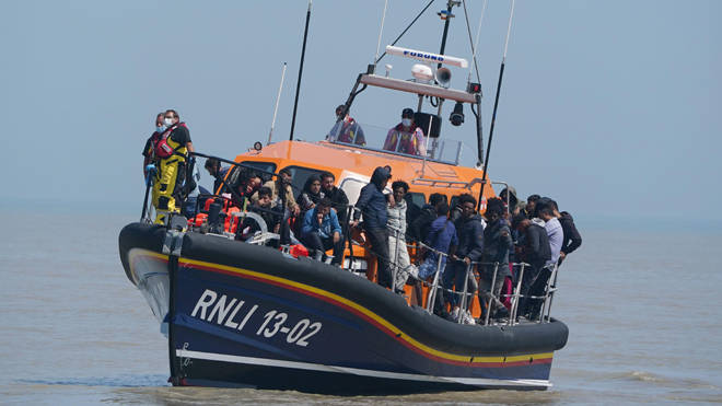 Migrants crossing from France come ashore aboard the local lifeboat at Dungeness in Kent
