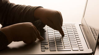 A child's hands on the keys of a laptop keyboard
