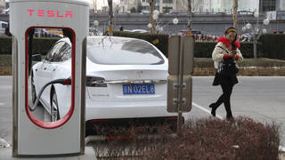 A woman walks past a Tesla car being charged in Beijing