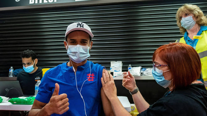 Rafael Nunez receives a first dose of the Pfizer vaccine at a pop-up mass vaccination clinic at Watford FC's Vicarage Road Stadium