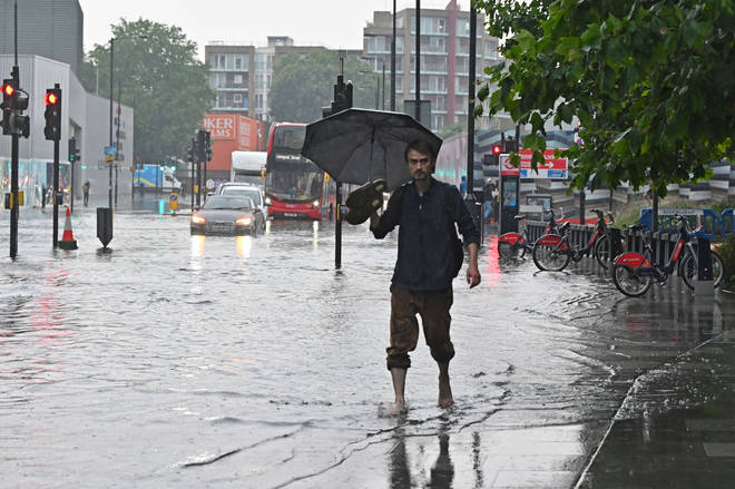 A pedestrian walks bare-footed along a flooded road in The Nine Elms district of London