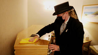 Funeral service worker cleans a coffin