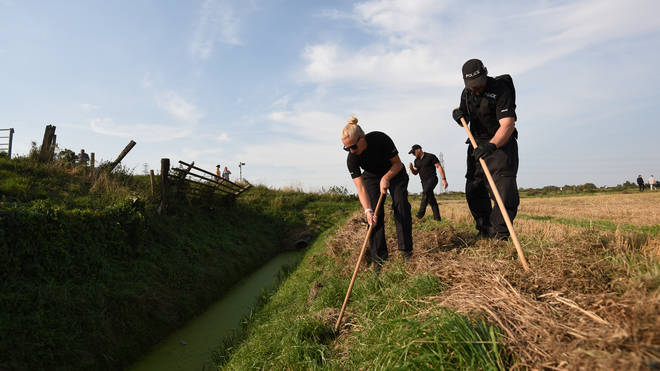 Police officers carry out a search after Bernadette's disappearance