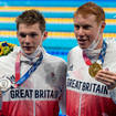 Duncan Scott, silver, and Tom Dean of Team GB, gold, show their medals after the men 200m freestyle final during the Tokyo 2020 Olympic Games