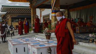 This photograph provided by UNICEF shows monks from Paro's monastic body perform a ritual as 500,000 doses of Moderna COVID-19 vaccine gifted from the United States arrived at Paro International Airport in Bhutan