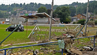 A damaged car and other debris strewn across a football pitch after flooding in Vaux-sous-Chevremont in Belgium on July 24