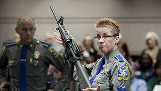 A police detective holds up a Bushmaster AR-15 rifle