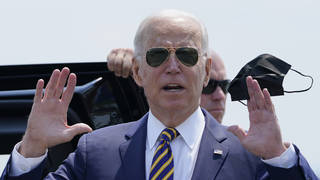 President Joe Biden holds a mask as he responds to a question as he arrives at Lehigh Valley International Airport
