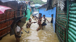 Children play in floodwaters at a Rohingya refugee camp