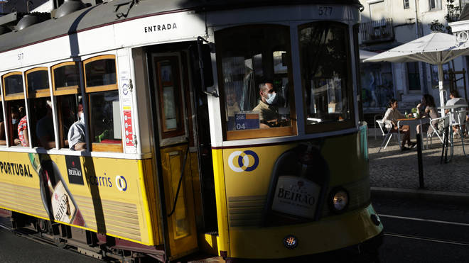 A tram conductor wearing a face mask drives through Lisbon's Graca neighbourhood