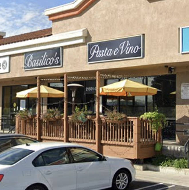 The sign is taped to the window of Basilico's Pasta e Vino, an Italian restaurant in Huntington Beach