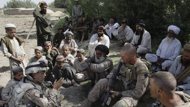 A translator for US Marines speaks with Afghan villagers in Helmand province