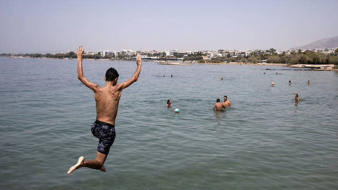 A youth jumps in the sea at a beach of Kavouri suburb, south-west of Athens