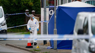 Police at the scene in High Wycombe where a man was found dead surrounded by a group