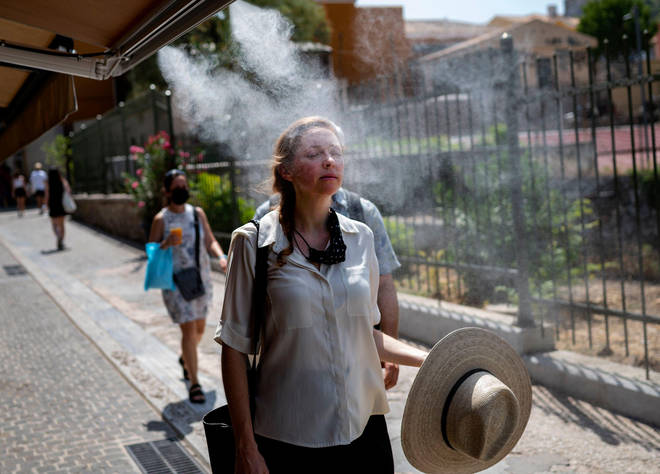 A tourist walks through a mist of water sprayed outside a café in Athens