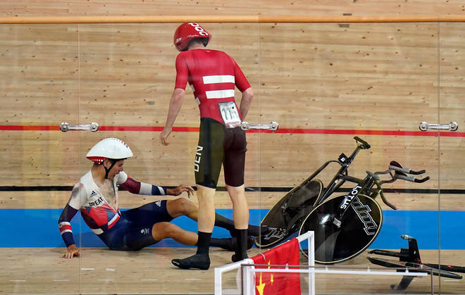 Great Britain's Charlie Tanfield picks up his bike after being crashed into by Denmark's Frederik Madsen in the men's team pursuit
