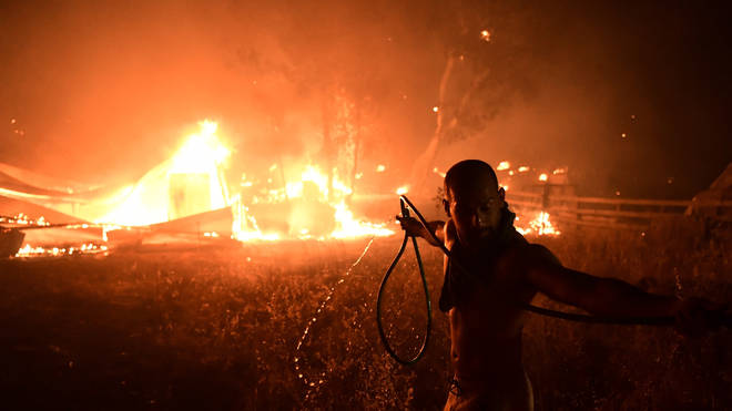 A man uses a water hose during a wildfire in northern Athens