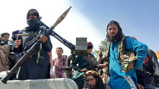 Taliban fighters sit over a vehicle on a street in Laghman province on Sunday