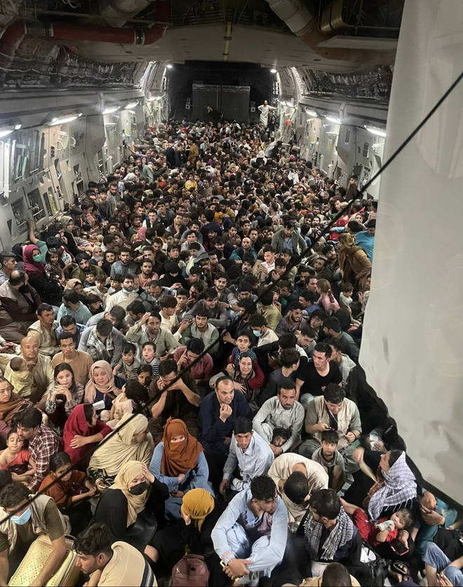 """A photograph showed hundreds of Afghan refugees crammed into an """"unplanned"""" rescue flight"""