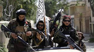 Taliban fighters display their flag on patrol in Kabul