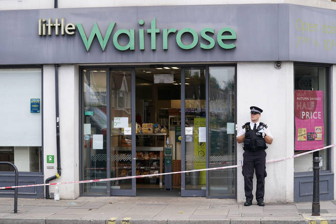 A police officer stands outside Little Waitrose on Fulham Palace Roa