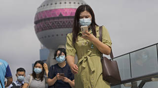 People wearing face masks using their smartphones as they walk on a bridge in Shanghai in China