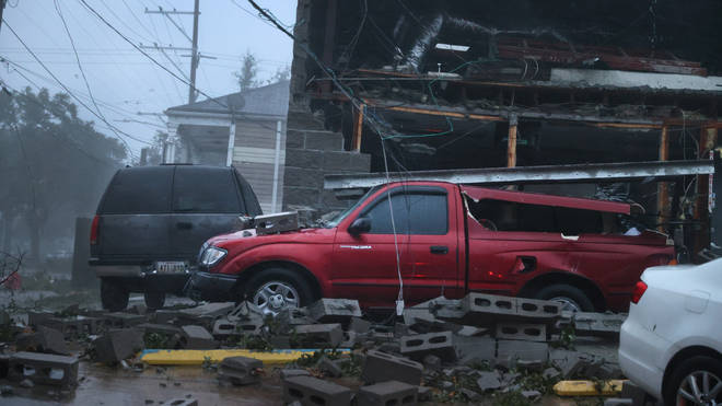 Vehicles are damaged after the front of a building collapsed in New Orleans during Hurricane Ida