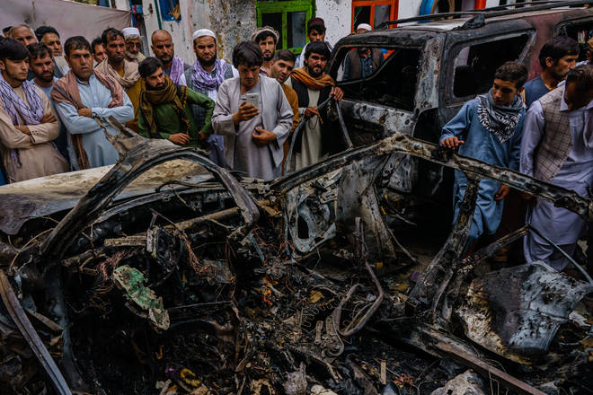 Relatives and neighbours of the Ahmadi family gather round the remains of a car that was hit by a US drone strike, reportedly killing 10 members of the family