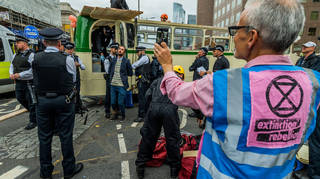 Police officers broke the windows of the bus while protesters attempted to stop them boarding
