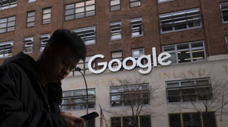 A person walks past a Google sign