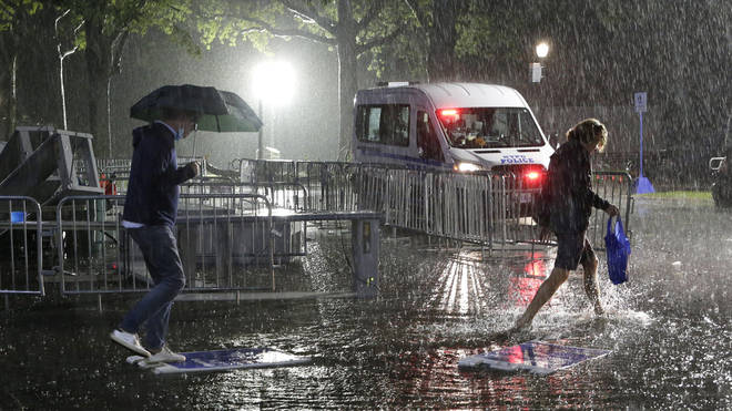 People wading through floodwaters on the street