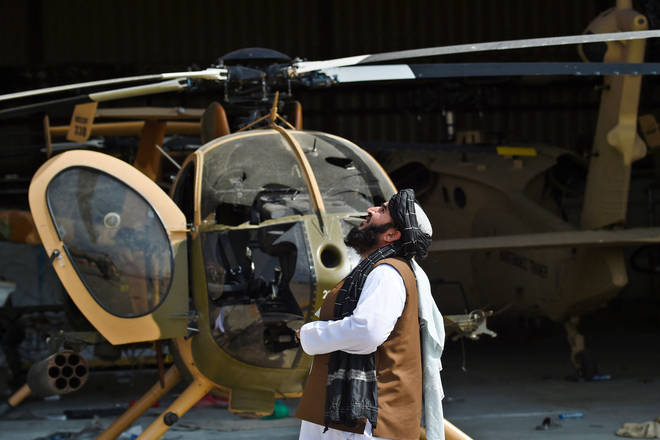 A member of the Taliban standing next to a damaged helicopter at the airport in Kabul.