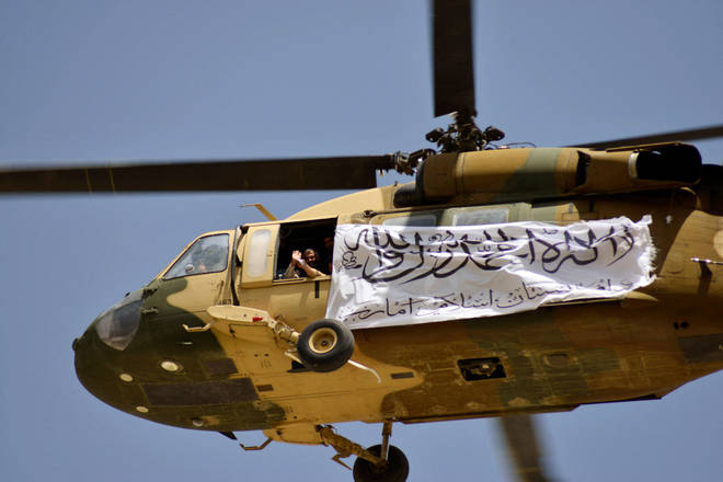 A helicopter displaying a Taliban flag flies above Taliban supporters gathered to celebrate the US withdrawal of all its troops out of Afghanistan.