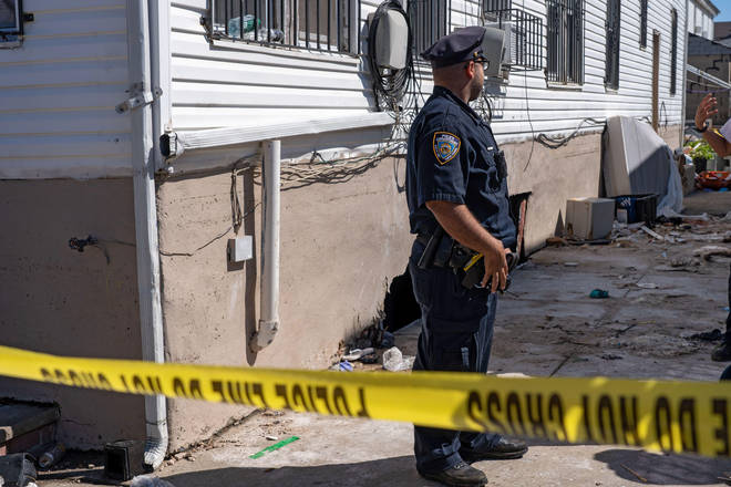 A police officer guards the house where two people died when their basement apartment in New York was flooded