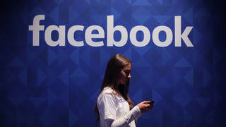 A woman on her phone underneath the Facebook logo