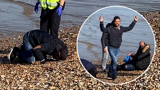 The group of migrants were seen kissing the beach and praying on the pebbles at Dungeness in Kent.