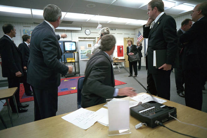 President Bush (centre) and his advisers watch television coverage of the attacks from a classroom at the school in Florida