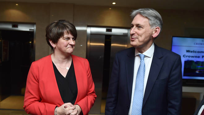 DUP leader Arlene Foster greets the UK Chancellor Philip Hammond as he arrives at the Democratic Unionist Party Conference