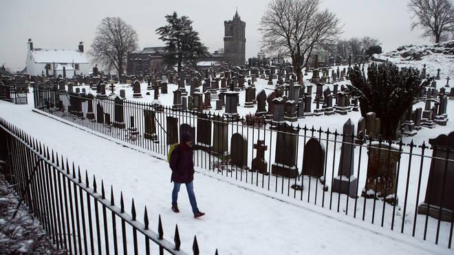 A man walks through a cemetery in the snow