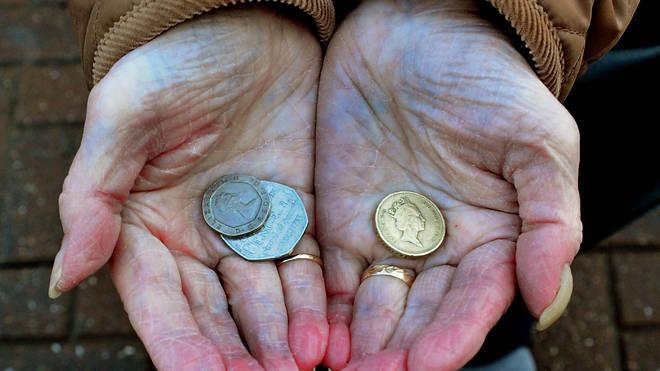 An elderly woman holding coins