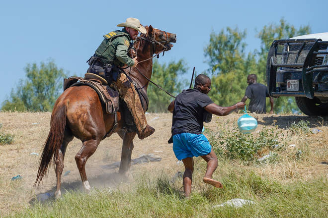 United States Border Patrol agent on horseback attempting to try and stop a Haitian migrant from entering an encampment on the banks of the Rio Grande near the Acuna Del Rio International Bridge in Del Rio, Texas