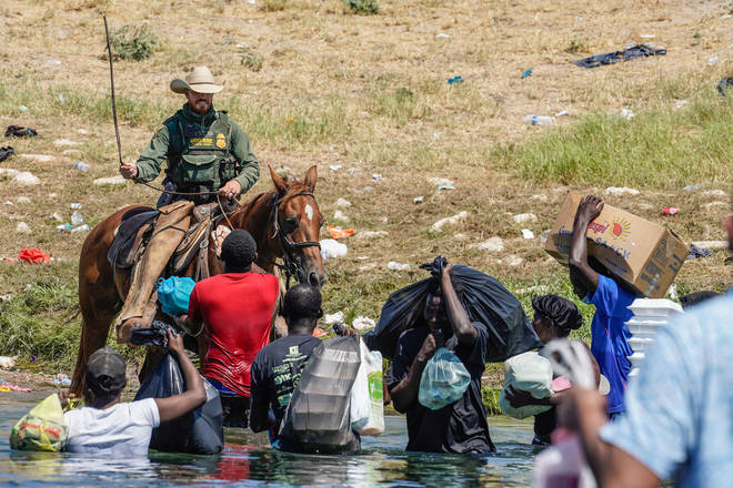 A United States Border Patrol agent on horseback uses the reins as he tries to stop Haitian migrants from entering an encampment on the banks of the Rio Grande
