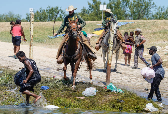 The agent pictured on horseback trying to stop a migrant from entering the US on the banks of the Rio Grande river