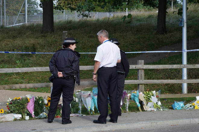 Police officers by floral tributes at Cator Park in Kidbrooke