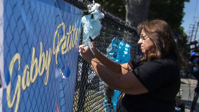 A woman places a decoration near a poster after attending the funeral home viewing of Gabby Petito at Moloney's Funeral Home in Holbrook, New York