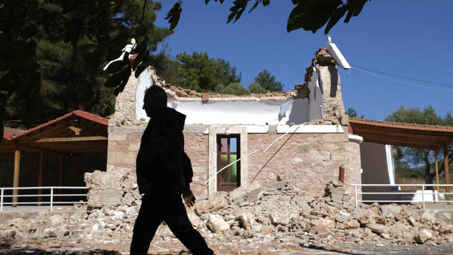 A man walks past a damaged Greek Orthodox chapel in Crete following the earthquake