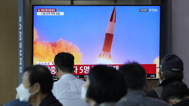 People watch a TV showing a file image of North Korea's missile launch during a news program at the Seoul Railway Station in Seoul, South Korea