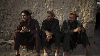 Three bearded Afghan men sit outside a mosque in Kabul on Monday