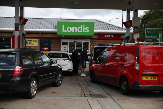Motorists queue to fill up their vehicles at a petrol station in London on Tuesday
